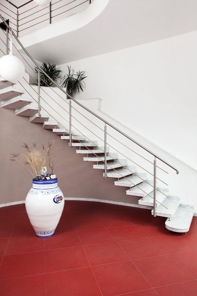 Scala a sbalzo con caposcala arrotondato in marmo Carrara bianco, ringhiera in acciaio inox