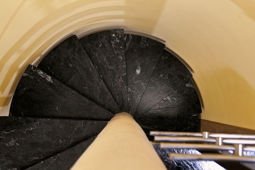 Scala a chiocciola in marmo nero, con colonna centrale