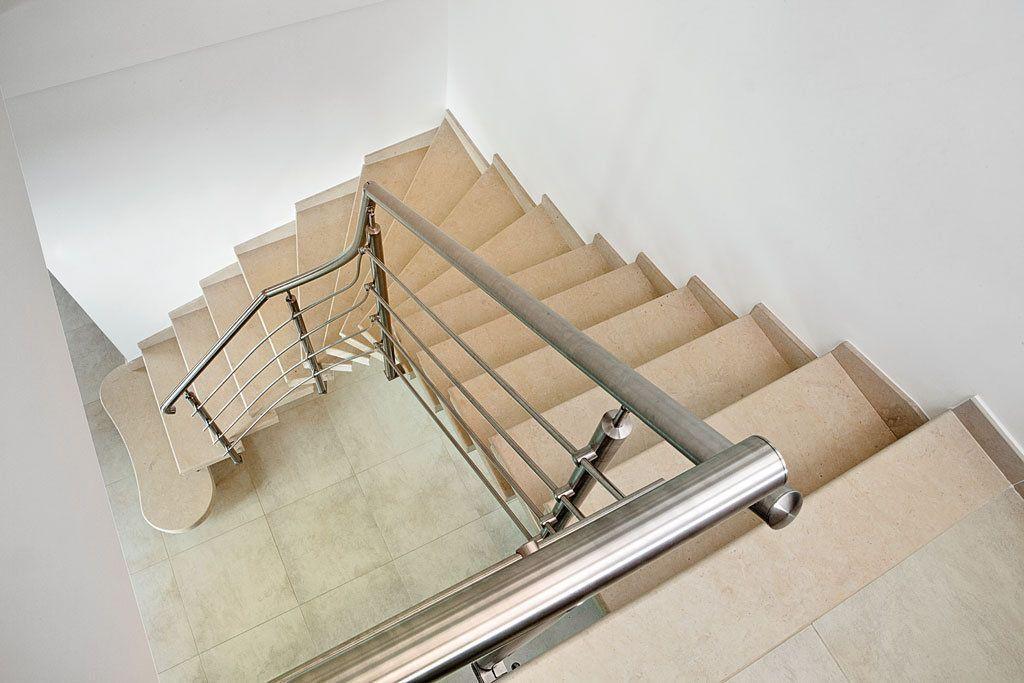 scala prefabbricata a sbalzo con ringhiera in acciaio inox rivestita in pietra beige